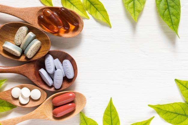緑の葉、フラットなレイsurと白い背景に木製スプーンのビタミン薬の様々な Premium写真